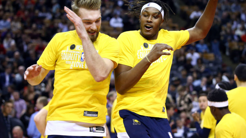 Domas Sabonis and Myles Turner greet each other and jump in the air in a Pacers game last season