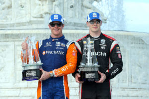 Scott Dixon and Josef Newgarden stand with trophies together on the podium in 2019