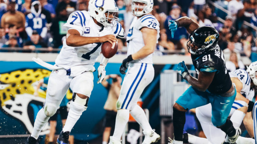 Jacoby Brissett evades a Jacksonville defender and looks down field as the Colts face the Jaguars