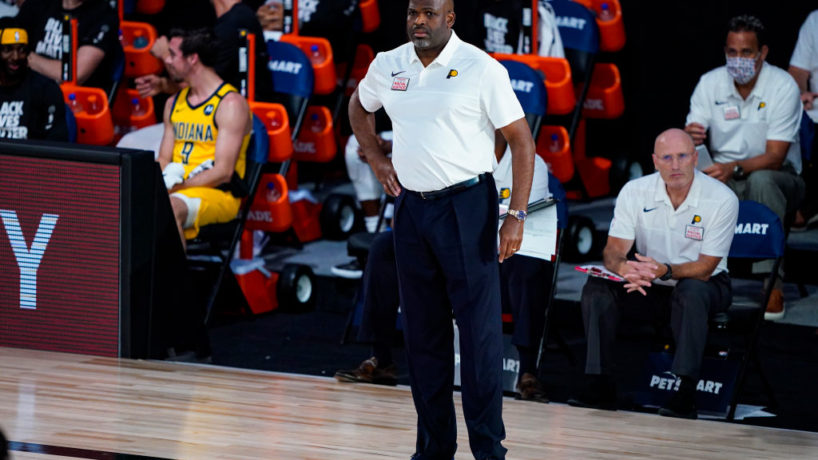Former Pacers head coach Nate McMillan stands on the floor while now former assistant Dan Burke sits and watches as the Pacers play in the Orlando bubble