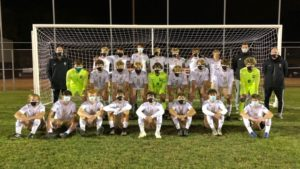 The Noblesville Boys Soccer team poses with their coaches in front of a soccer goal