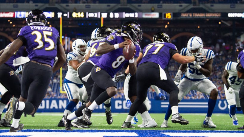 Lamar Jackson looks to the right behind his offensive line as the Colts defense chases after him in his own end zone