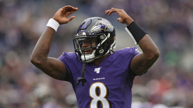 Ravens QB-Lamar Jackson raises his hands to the sky.