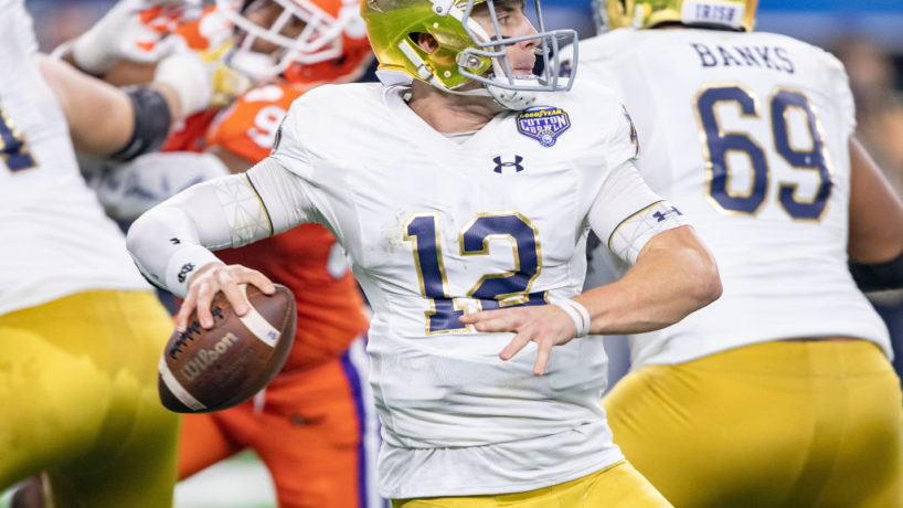 Ian Book looks downfield and prepares to throw a pass for Notre Dame as the Clemson pass rush attacks his offensive line