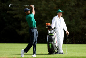 Tiger Woods swings and looks at his shot with his caddy behind him in a practice round for the 2020 Masters at Augusta