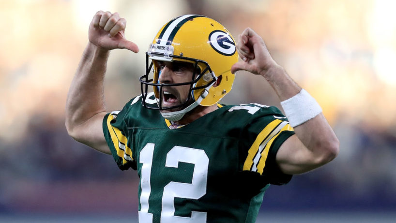 Packers QB-Aaron Rodgers points to his jersey.