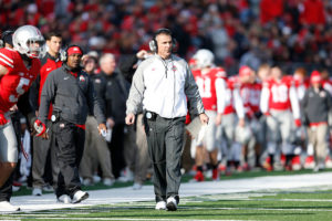 Urban Meyer coaches in a game in front of his sideline with players and coaches behind against the Indiana Hoosiers