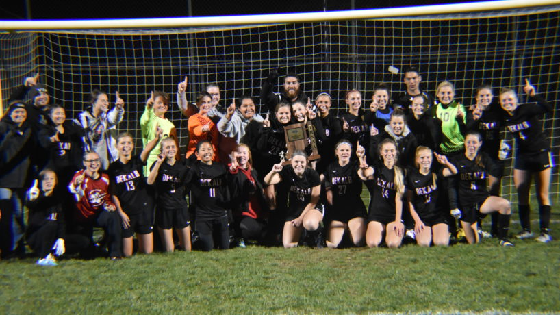 The DeKalb Girls Soccer team poses with their coaches in front of a soccer goal