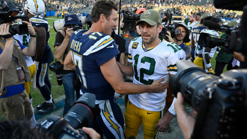 In the middle of a circle of cameras and reporters, Philip Rivers and Aaron Rodgers shake hands following their game between the Chargers and Packers last November