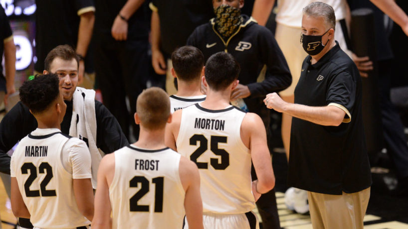 Purdue coach Matt Painter huddles around a group of players in a timeout at Mackey Arena