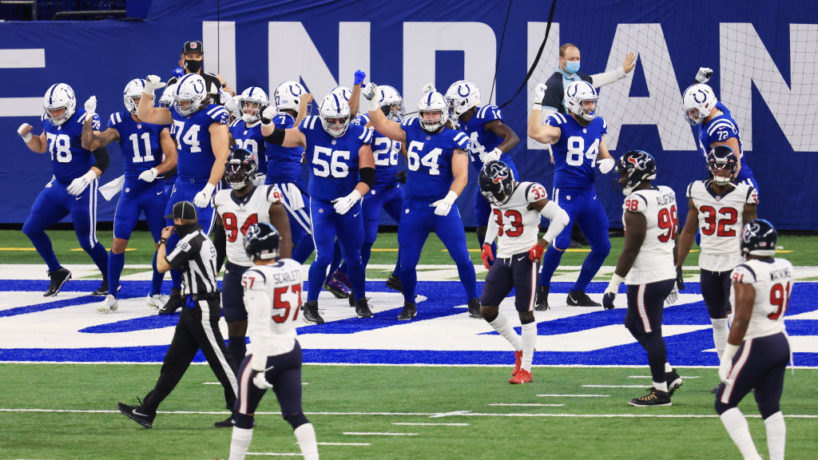 Five Houston Texans players stand in front of the endzone dejected with the entire Indianapolis Colts offense dancing behind them after a touchdown