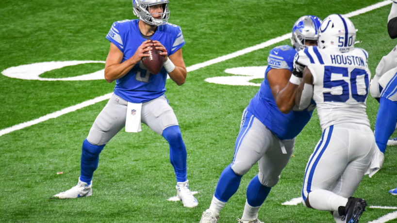 Matthew Stafford drops back to pass in a game against the Indianapolis Colts as Justin Houston drives in from the other side colliding with an offensive lineman