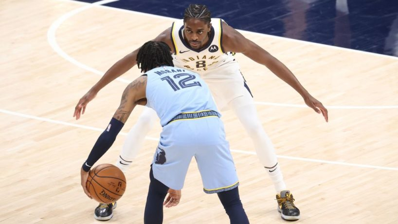 Pacers forward Justin Holiday stretches out his arms to guard Grizzlies star Ja Morant