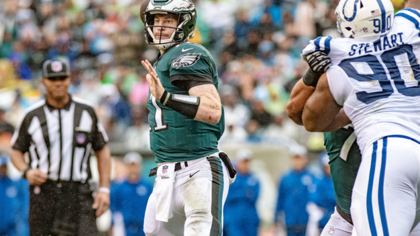 Carson Wentz throws the football behind an offensive lineman blocking Colts rusher Grover Stewart