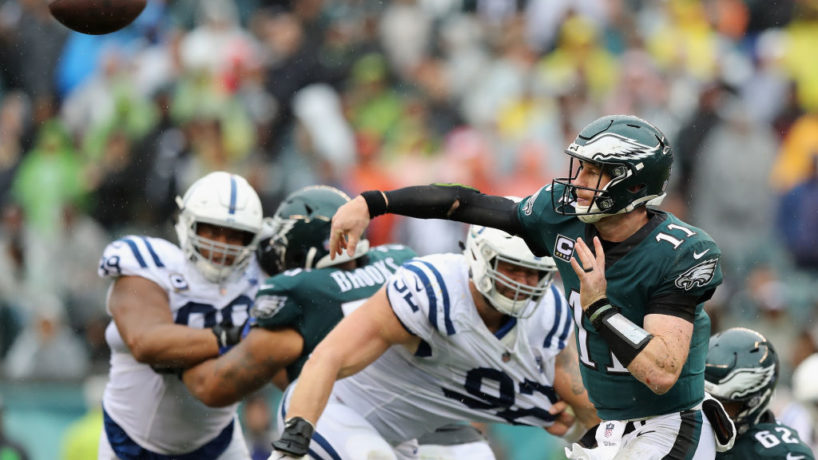 Carson Wentz launches a pass looking to his left with two Colts pass rushers heading in his direction