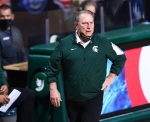 Tom Izzo watches his Michigan State team on the sideline with one hand on his hip