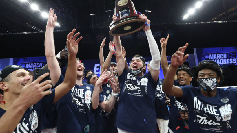 The Gonzaga Bulldogs huddle together and lift their regional trophy as they win in the Elite 8 against USC