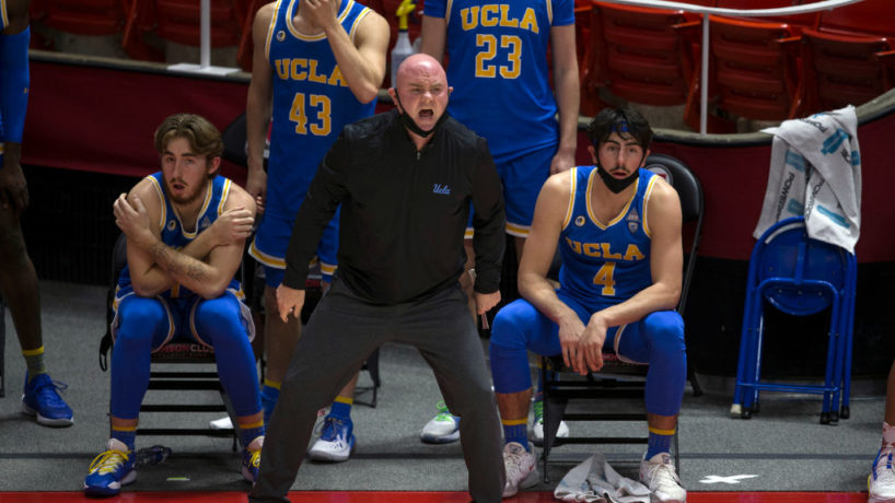 UCLA Assistant Michael Lewis stands in front of the team bench with players behind him as he shouts orders to the guys in the floor