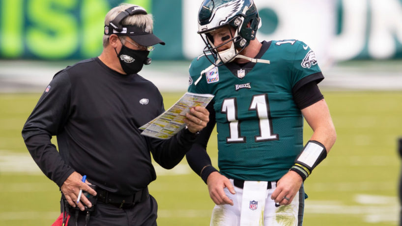 Carson Wentz and Doug Pederson talk during a game.