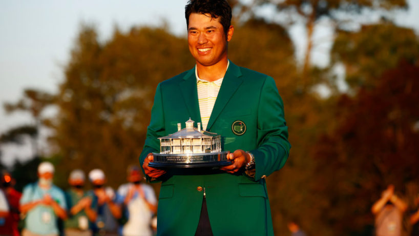 Hideki Matsuyama poses in front of cameras and fans while wearing his Green Jacket and lifting the trophy after his Masters win
