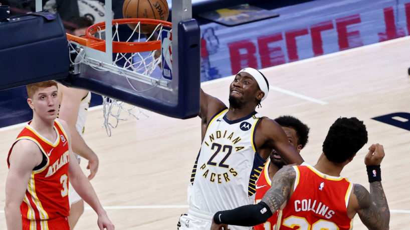 Caris LeVert rises up to the rim for a slam dunk between two Atlanta Hawks players