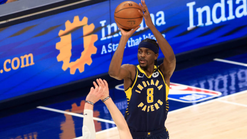 Justin Holiday rises to shoot from 3 over a Milwaukee Bucks defender at Bankers Life Fieldhouse