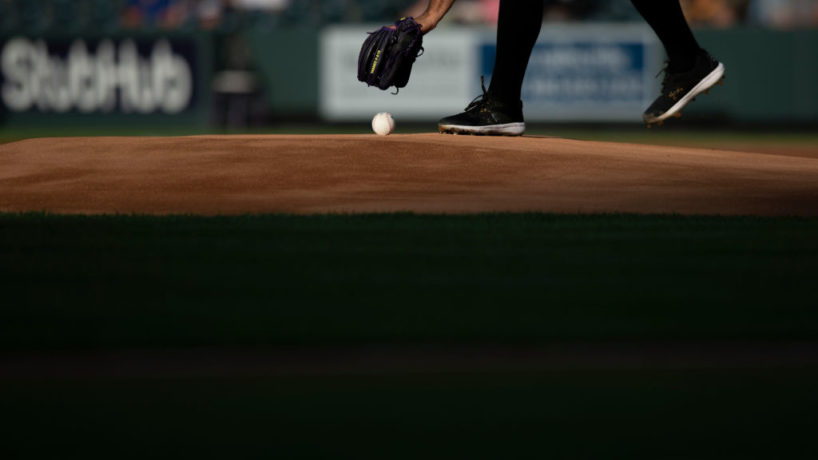 A pitcher climbs the mound in an MLB ballpark and picks up the baseball with his glove
