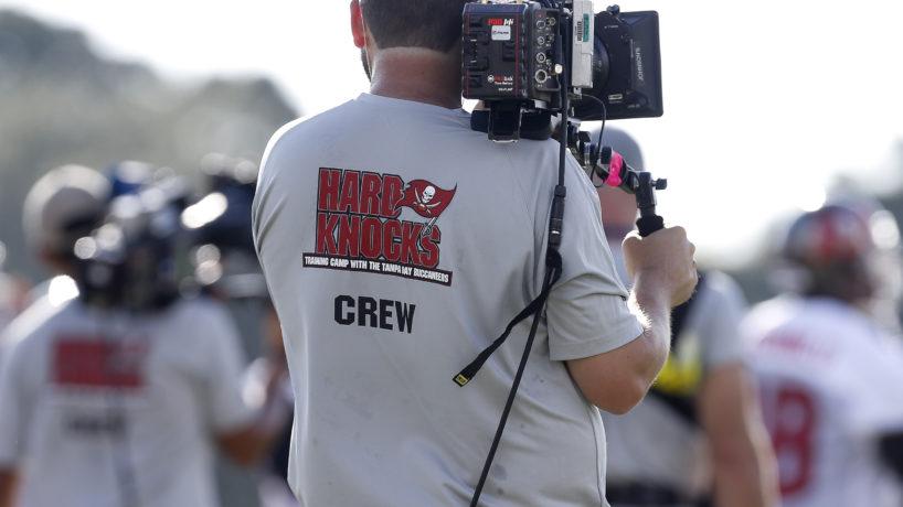 back of a Hard Knocks crew member holding a camera