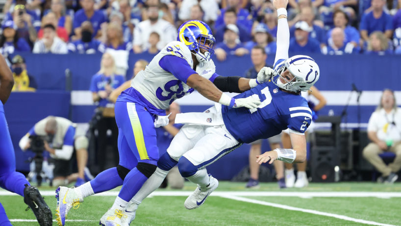 Carson Wentz being pushed by Aaron Donald has he throws the football
