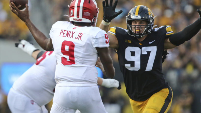 Michael Pennix Jr. throwing football with Iowa defender running at him