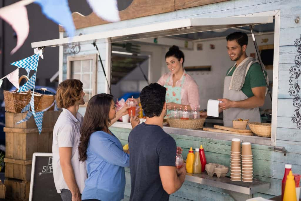 People being served at a food truck
