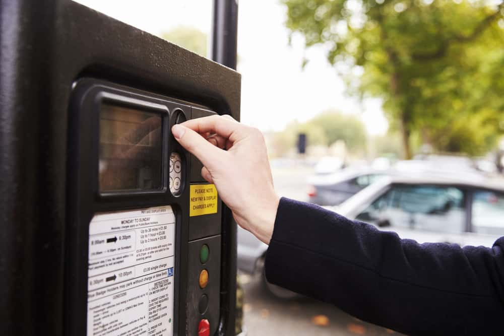 putting money into a parking meter