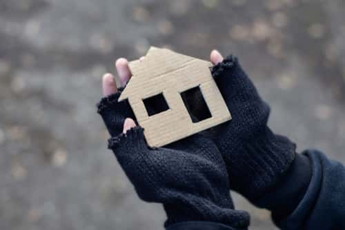 Hands holding a cardboard house