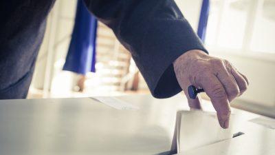 ballot being put into a ballot box