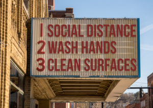 "Movie theater sign that reads: ""1. Social Distancing, 2. Wash Hands, 3. Clean Surfaces"""
