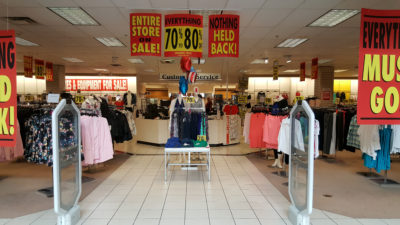 Retail store with signs. Entire store on sale. Everything 70% - 80%. Nothing held back. Everything must go.