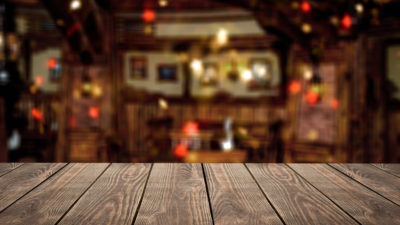 Blank wooden table top in front of abstract blurred restaurant lights