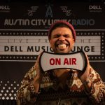 Dell Music Lounge with Devon Gilfillian: Devon Gilfillian holding on-air sign
