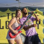 Man and woman holding an inflatable guitar and microphone