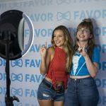 "Women posing in front of ""favor"" sign"