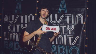 "Adam Melchor holding ""on-air"" sign"