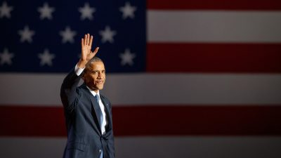 Barack Obama waving in front of American flag