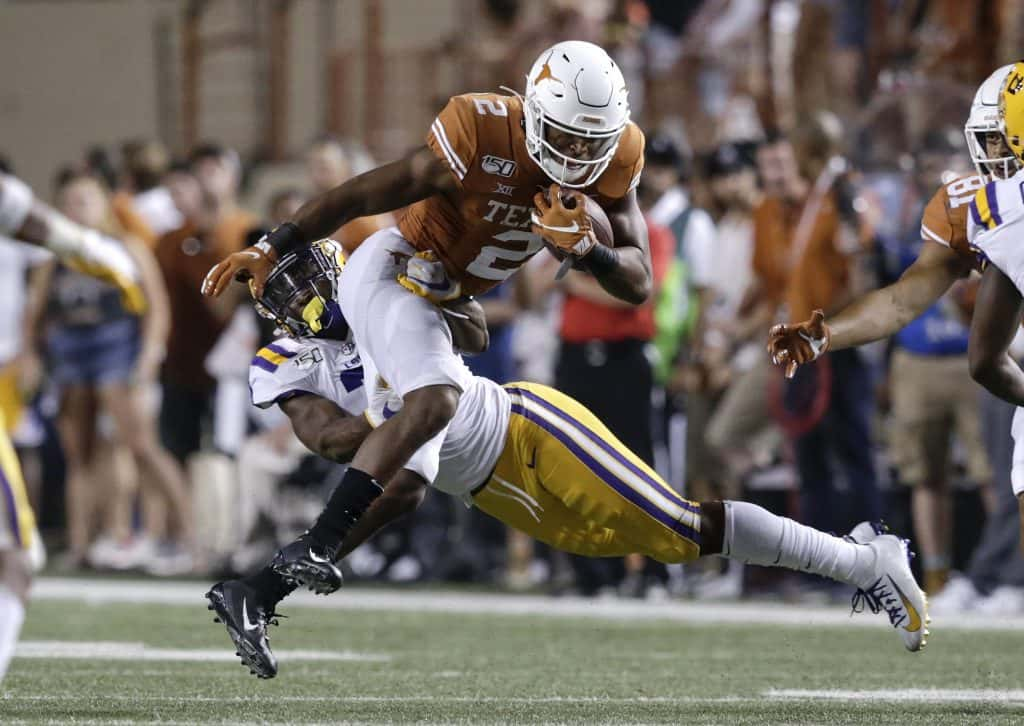 UT longhorn getting tackled by a LSU Tiger