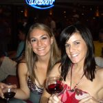 #TBT Bud Light Party Cruise : Deb and former 'Sorority Intern' Cassandra at the Bahamas Bud Light Party Cruise from 2009 holding a glass of wine in front of a Bud Light sign.