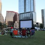 Summer Cinema Series 2019: Screen at Summer Cinema and family sitting in lawn chairs