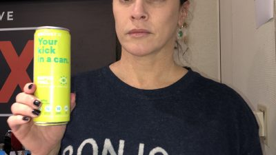 Deb holding up a can of eboost energy drink with a wide-eyed look on her face