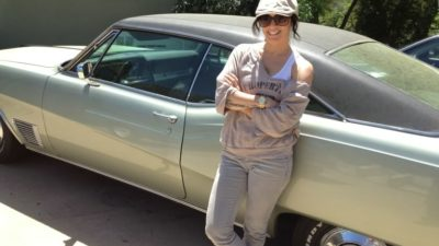Deb standing in front of her classic Buick Wildcat muscle car