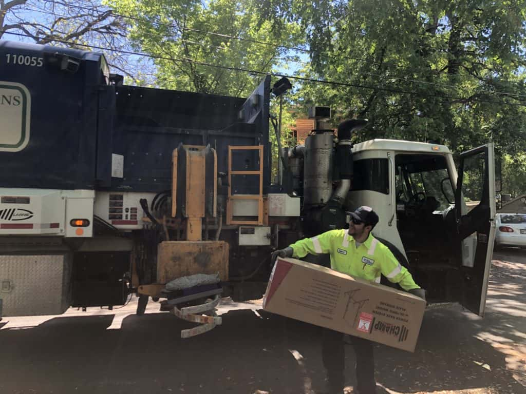 a garbage man throwing a cardboard box into a garbage truck