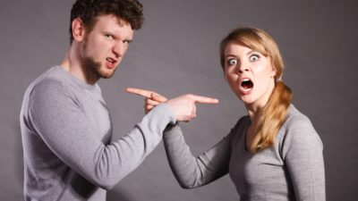 stock image of an arguing couple pointing fingers at each other