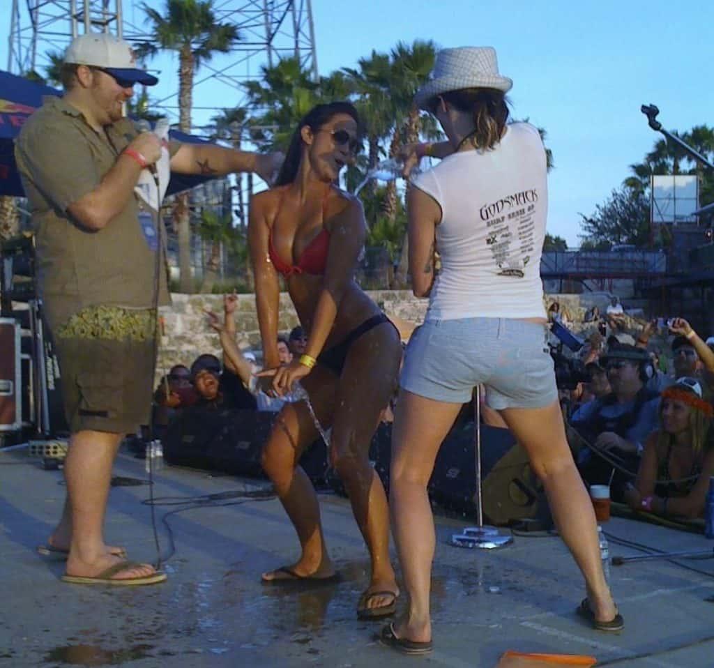 Jason and deb pouring water in intern annalin at surf sesh